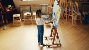 High angle view of professional painter working alone indoors in studio painting picture then stepping back and. Evaluating her work. People, hobby and stock video