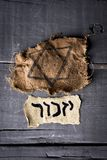 Jewish badge and hebrew word yizkor, for remember. High angle view of a ragged jewish badge and a yellowish piece of paper with the word yizkor, remember in Stock Photos