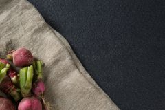 High angle view of red radishes on burlap. Over slate Stock Photography