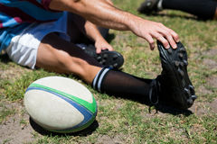 High angle view of rugby player touching toes. While sitting on grassy field Stock Image