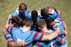 High angle view of rugby team making  huddle while standing at playing field. On sunny day Royalty Free Stock Images