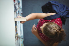 High angle view of schoolgirl selecting book from bookshelf in library. At school Stock Photo