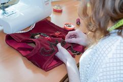 Seamstress sitting at table with sewing machine and embroiders red vest in studio royalty free stock photos