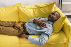 High angle view of senior african american man. Sleeping with book on sofa stock image