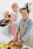 high angle view of senior couple cooking together at kitchen and looking stock photos