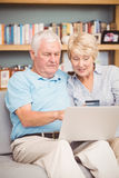 High angle view of senior couple using laptop while sitting on sofa Royalty Free Stock Photos