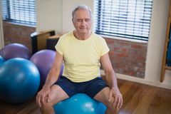 High angle view of senior male patient sitting on exercise ball with eyes closed Stock Photos