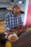 High angle view of senior man using laptop in kitchen Royalty Free Stock Photo