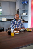 High angle view of senior man using tablet. While sitting at table in kitchen Royalty Free Stock Photography