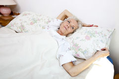 High angle view of senior woman looking away while lying in bed at home Stock Photography