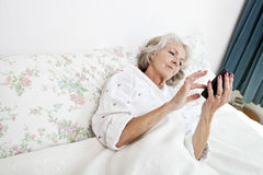 High angle view of senior woman using smart phone in bed at home Royalty Free Stock Photos