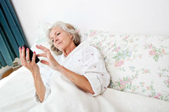 High angle view of senior woman using smart phone in bed at home Royalty Free Stock Photography