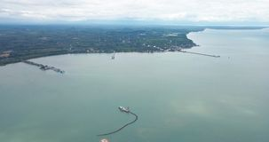 High angle view shows the coastal town by the gulf of Thailand. High angle view shows the coastal town a private compay `s sand extractionship is sucking sand stock video footage