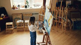 High angle view of young blonde painting bright marine landscape working alone in studio holding palette and brush. Nice stock video