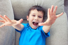 High angle view of a small boy with raised hands lying on sofa Royalty Free Stock Photos