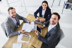 High angle view of smiling businesspeople working with gadgets. In office stock images