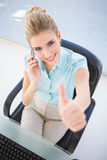 High angle view of smiling businesswoman on the phone giving thu Royalty Free Stock Photography