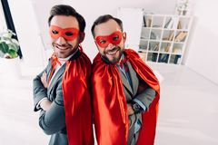 High angle view of smiling handsome super businessmen in masks and capes with crossed arms. In office royalty free stock images
