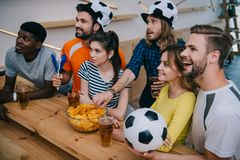 high angle view of smiling multicultural group of friends in soccer ball hats drinking beer and watching football match stock image