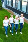 High angle view of smiling women with breast cancer awareness ribbons walking together on green. Lawn stock photography