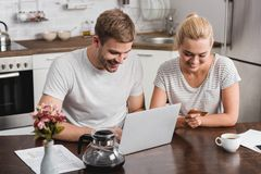 High angle view of smiling young couple with credit card using laptop. At home stock images