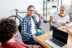 High angle view of smiling young coworkers eating pizza together while working together. In office royalty free stock photography