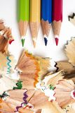 Pencil crayons and shavings of different colors. High angle view of some pencil crayons of different colors and a pile of fan-shaped shavings of different colors Royalty Free Stock Image