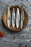 Raw sardines on a rustic wooden table. High angle view of some raw sardines in a boxwood plate placed on a gray rustic wooden table sprinkled with peppercorns stock photo