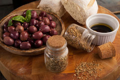 High angle view of spices by black olives in plate. On wooden table Royalty Free Stock Photography