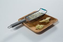 High angle view of steel grater and ginger on wooden plate. Over white background Royalty Free Stock Photography