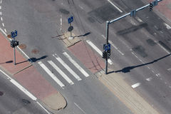 High angle view of a street intersection. High angle view of an empty street intersection with cross walk markings, traffic signal lights Royalty Free Stock Image
