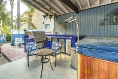 High angle view of a stylish outdoor kitchen on a brick patio wi. Th a built in gas barbecue,rug and dining table with hanging chandelier. Wonderful California Royalty Free Stock Images