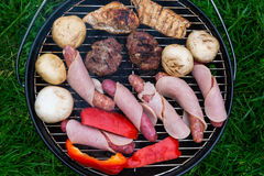 High angle view, succulent steaks,burgers,sausages and vegetables cooking on a barbecue over the hot coals on a green lawn outd Stock Images