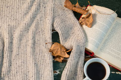 High angle view of sweater by open book and coffee cup. On table Stock Photos