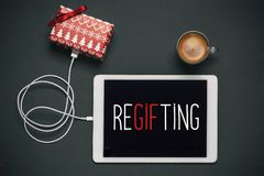 Gift and text regifting in a tablet. High-angle view of a tablet with the word regifting in its screen, connected to a gift by a cable, and a cup of coffee stock photos