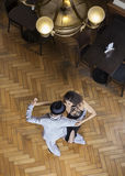 High Angle View Of Tango Dancers Performing On Wooden Floor. High angle view of male and female tango dancers performing on hardwood floor at restaurant Royalty Free Stock Images