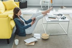 High angle view of teenage girl. Using smartphone while sitting on carpet and studying at home royalty free stock photos