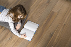High angle view of teenage girl reading book on floor at home Stock Photo