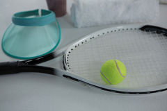 High angle view of tennis ball on racket by sun visor. Against white background Stock Photo