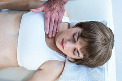 High angle view of therapist performing reiki over woman. High angle view of male therapist performing reiki over women at health club Royalty Free Stock Images