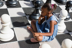 High angle view of thoughtful girl sitting by chess pieces Royalty Free Stock Photos