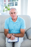 High angle view of thoughtful senior man with clipboard Stock Image