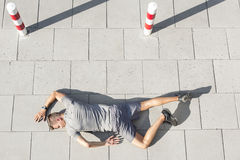 High angle view of tired sporty man lying on sidewalk Stock Photo