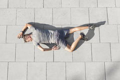 High angle view of tired sporty man lying on tiled sidewalk Stock Photography