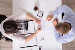 Two Businesspeople Analyzing Bill royalty free stock photo