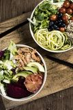 Buddha bowls on a wooden table. High angle view of two different buddha bowls, made with lettuce, cornsalad, quinoa, zucchini spaghetti, blueberries, beet stock photos