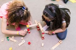 High-angle view of two pre-school girls sharing wooden toy blocks Royalty Free Stock Photos