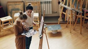 High angle view of two young women art teacher and student mixing colors on palette, talking and smiling then painting stock video