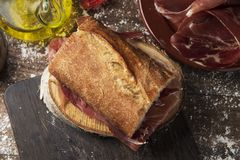 Spanish bocadillo de jamon, serrano ham sandwich. High angle view of a typical spanish bocadillo de jamon, a serrano ham sandwich, on a rustic wooden table, next Royalty Free Stock Photos