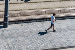 High angle view of unidentified male runner jogging on road. Budapest, Hungary - August 14, 2017: High angle view of unidentified male runner jogging on road in Royalty Free Stock Images